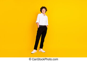 Photo of friendly sweet school boy wear white shirt smiling arms pockets walking isolated yellow color background