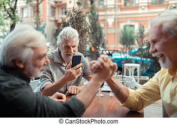 Grey-haired man making photo of friends arm-wrestling
