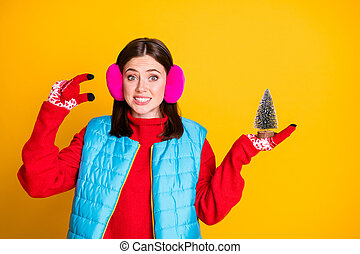 Photo of frustrated girl feel guilty about choosing little christmas evergreen tree wear pink sweater isolated over shine color background