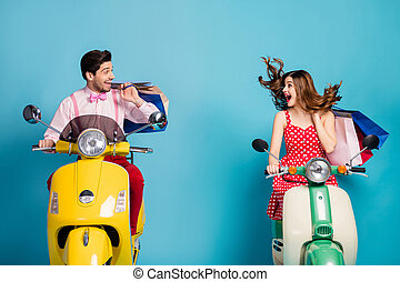 Photo of funky excited lady guy couple drive rent retro moped travelers hold hands many shopping packs good mood addicted shoppers abroad vintage clothes isolated blue color background