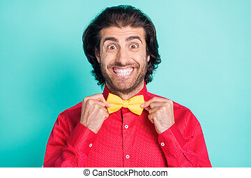 Photo of funky funny cheerful smiling handsome gentleman adjusting bow tie isolated on teal color background