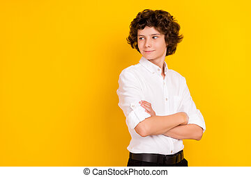 Photo of funny dreamy school boy wear white shirt smiling arms crossed looking empty space isolated yellow color background