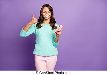 Photo of funny pretty lady hold telephone raise thumb finger up advising smart phone season sale price wear casual fluffy pastel sweater pink pants isolated purple color background
