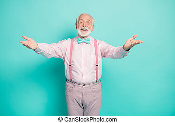 Photo of funny stylish grandpa hold open arms good cheerful mood want to hug grandchildren meeting wear pink shirt suspenders bow tie pants isolated bright teal color background