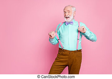 Photo of funny stylish grandpa positive emotions before senior party meeting touch hold fingers suspenders wear shirt violet bow tie brown pants isolated pink pastel color background