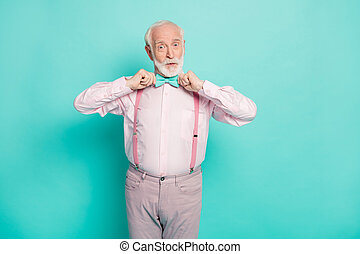 Photo of funny stylish look grandpa hold hands buttoning fixing necktie good cheerful mood wear pink shirt suspenders bow tie pants isolated bright teal color background