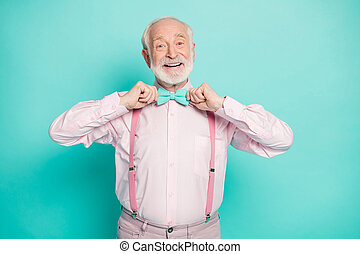 Photo of funny stylish look grandpa hold hands buttoning necktie positive emotions wear pink shirt suspenders bow tie pants isolated bright teal color background