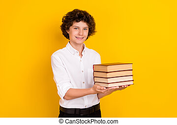 Photo of funny sweet school boy wear white shirt smiling holding book stack isolated yellow color background