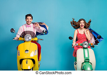 Photo of funny two people lady guy drive rent retro moped travelers hold hands many shopping packs good mood addicted shoppers abroad vintage clothes isolated blue color background