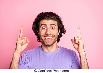Photo of funny young guy direct fingers up empty space wear purple shirt isolated pastel pink color background