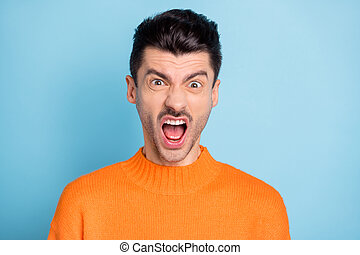 Photo of furious handsome guy open mouth fuming yell noise wear sweater isolated on blue color background