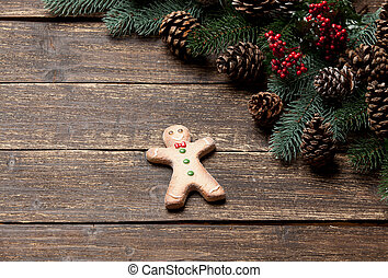 photo of gingebread man near christmas decorations on the wonderful brown wooden background