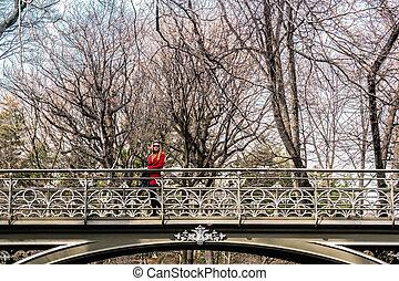 Girl crossing a bridge at Central Park in Manhattan, New York City