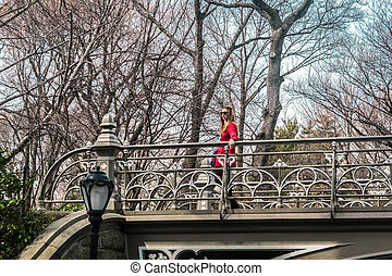 Girl crossing a bridge at Central Park in Manhattan, New York City
