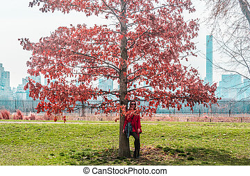 Girl in front of trees at Central Park in Manhattan, New York City