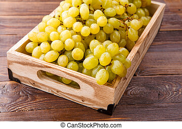 Photo of green grapes in wooden box
