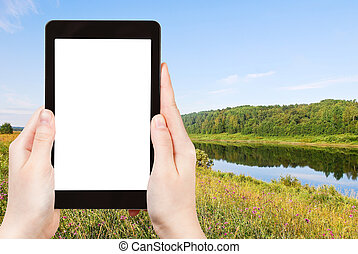 travel concept - tourist photograph green grass on riverbank in summer day, Vologda, Russia on tablet pc with cut out screen with blank place for advertising logo