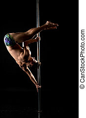 Photo of guy performs acrobatic trick on pole
