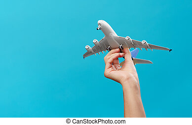 Photo of hand with airplane on empty blue background in studio.