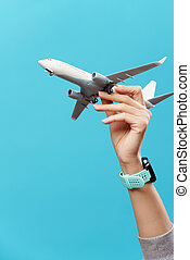 Photo of hand with airplane on empty blue background