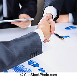 Photo of handshake  business partners after signing promising contract Close-up