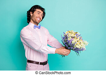 Photo of handsome beaming gentle man dressed pink outfit congratulating you birthday presenting bunch flowers look empty space arms isolated teal color background