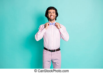 Photo of handsome beaming gentle man dressed pink outfit preparing birthday party fixing bow tie arms isolated teal color background