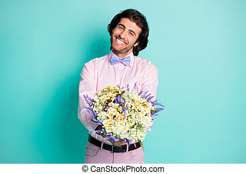 Photo of handsome beaming gentle man dressed pink outfit preparing present you bouquet beautiful flowers isolated teal color background
