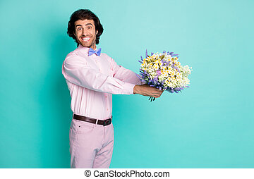Photo of handsome beaming gentle man wear pink outfit presenting bouquet flowers birthday party isolated teal color background