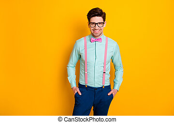 Photo of handsome cool clothes guy boyfriend standing self-confidently hands pockets beaming smile wear specs shirt suspenders bow tie trousers isolated yellow color background