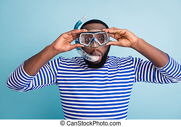 Photo of handsome funny dark skin guy tourist diving underwater mask see colorful fish corals breathing tube floating deep wear striped sailor shirt isolated blue color background