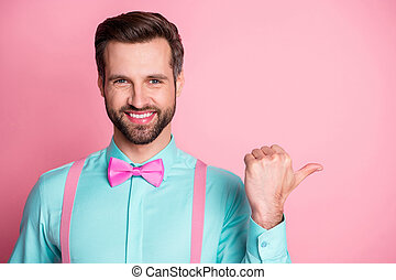 Photo of handsome guy trend clothes direct thumb finger side empty space toothy smile showing novelty banner wear shirt suspenders bow tie isolated pastel pink color background