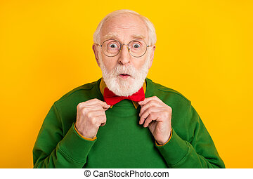 Photo of handsome impressed mature man dressed pullover arms bow tie glasses big eyes isolated yellow color background