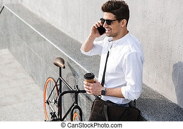 Photo of handsome man 30s wearing sunglasses, drinking takeaway coffee and talking on mobile phone while standing with bicycle along wall outdoor