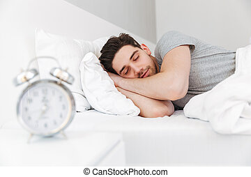 Photo of handsome man having stubble and wearing casual clothes, sleeping at home in bed with clock on nightstand