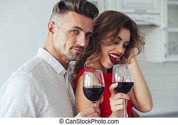 Photo of handsome man hug his woman and looking camera while drinking wine