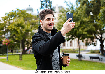 Photo of handsome man taking selfie photo on smartphone and drinking takeaway coffee while walking through city park
