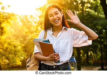 Photo of happy asian student woman with exercise books waving hand while walking in green park