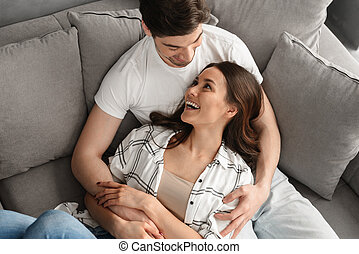 Photo of happy atractive man and woman smiling, and hugging while resting together in apartment
