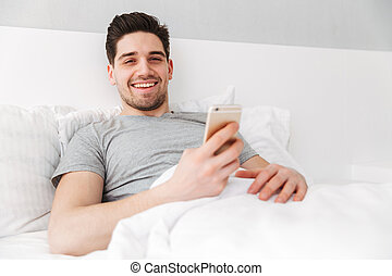 Photo of happy awake man in t-shirt smiling while lying alone in bed with white linen, and holding golden cell phone