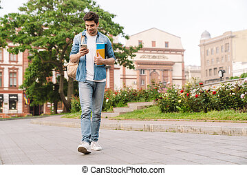 Photo of happy handsome man smiling and using cellphone while walking
