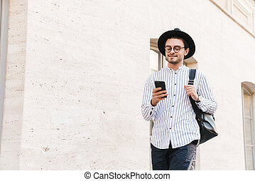 Photo of happy handsome man typing on cellphone and smiling while walking in city street