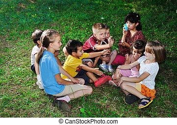 Photo of happy kids playing and blowing soap bubbles