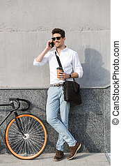 Photo of happy man 30s wearing sunglasses, drinking takeaway coffee and talking on mobile phone while standing with bicycle along wall outdoor