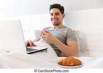 Photo of happy man in casual clothes having breakfast, while lying in bed with laptop and cup of coffee
