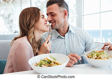 Photo of happy romantic couple having dinner and eating salats together, while resting in city cafe during lunch break