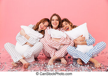 Photo of happy women 20s wearing leisure clothings sitting barefoot on floor with legs crossed and hugging pillows during girlish sleepover, isolated over pink background