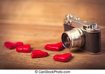 photo of heart shaped toys and retro camera on the wonderful brown wooden background
