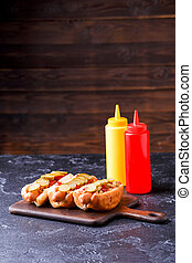 Photo of hotdogs on cutting board at table