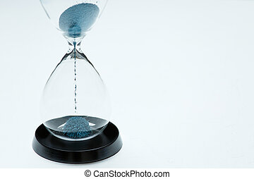 Photo of hourglass with blue sand on isolated white background,